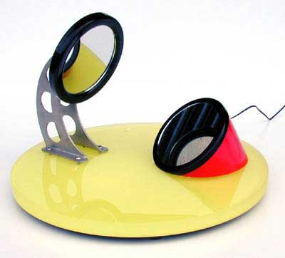 Lean down between the two mirrors and look into the lower one to see the reflection of the upper mirror. Move your head until the small lamp in the upper mirror is shining into your ear. This will allow you to study the patterns in the folds of your ear, which your DNA makes unique to you.