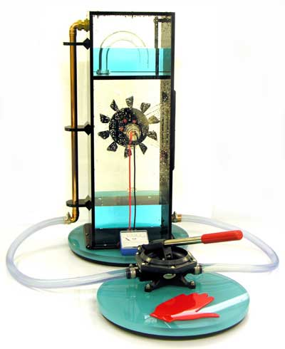 This is one of our new designs. Use the red lever to pump the water up into the upper tank. Once it reaches a certain level it will automatically siphon down onto the turbine wheel. As the wheel turns it powers the generator which is connected to a milliammeter.