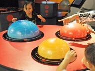 "Learning about Atmospheric Circulation  Here we have a young group of Malaysian children playing with this very appealing exhibit.   The suspended particles in a ""flow-tracing fluid"" reveal every detail of the turbulent patterns."